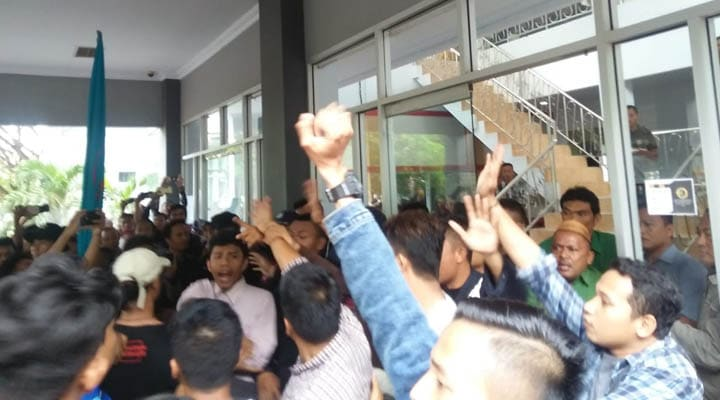 Peserta unjuk rasa Aliansi Mahasiswa UNG Bersatu sempat saling dorong dengan petugas security di depan pintu kantor BAKP UNG. Kondisi itu mengakibatkan salah satu pintu kacah pecah. (muhajir/gopos)
