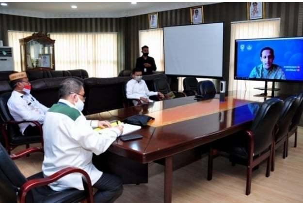 Wagub Gorontalo H. Idris Rahim (kiri) didampingi Kadis Dikbudpora, Yosef Koton, mendengarkan arahan Mendikbud Nadiem Makarim pada rakor kebijakan pembelajaran pada masa pandemi Covid-19 melalui video konferensi di ruang kerja Wagub, Rabu (2/9/2020). (Foto : Haris – Humas)