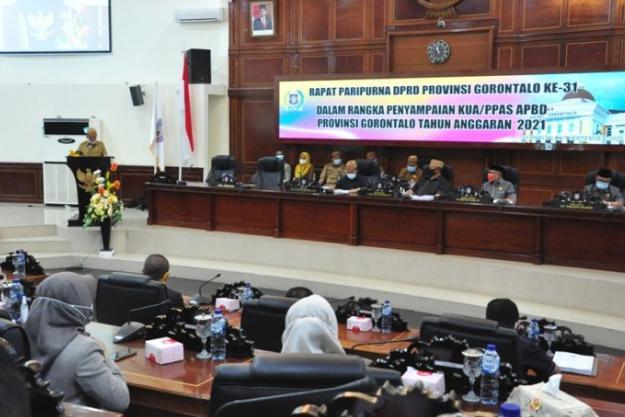 Wagub Gorontalo H. Idris Rahim (kiri) memberikan sambutan pada rapat paripurna DPRD ke-31 dalam rangka penyampaian KUA PPAS Tahun Anggaran 2021 di ruang rapat DPRD Provinsi Gorontalo, Senin (21/9/2020). (Foto : Haris – Humas)