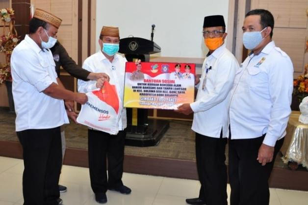 Wagub Gorontalo H. Idris Rahim (kedua kiri), menyerahkan secara simbolis bansos untuk korban bencana banjir bandang dan tanah longsor kepada Sekda Bone Bolango, Ishak Ntoma, di aula rumah jabatan Wagub, Rabu (23/9/2020). (Foto : Haris – Humas)