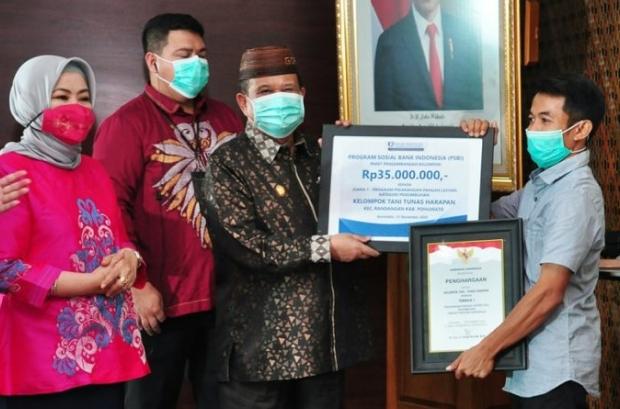 Wagub Gorontalo H. Idris Rahim (tengah) menyerahkan hadiah kepada juara pertama lomba P2L tingkat Provinsi Gorontalo untuk Kategori Penumbuhan yang diraih oleh Kelompok Tani Tunas Harapan, Kabupaten Pohuwato, di aula Kantor Perwakilan BI Gorontalo, Kamis (12/11/2020). (Foto : Haris – Humas)