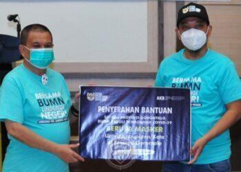Ketua Satgas Bencana BUMN Gorontalo, Teddy Indra Yudhana (kanan), menyerahkan secara simbolis bantuan masker untuk kabupaten/kota se Provinsi Gorontalo kepada Wagub Gorontalo H. Idris Rahim di aula rumah jabatan Wagub, Sabtu (26/12/2020). (Foto : Haris – Humas)