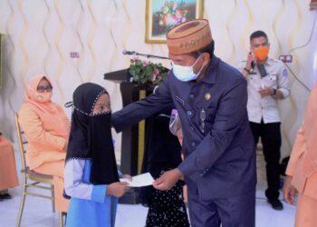 Sekretaris Daerah Provinsi Gorontalo Darda Daraba menyerahkan bantuan beasiswa kepada salah satu pelajar anak anggota DWP yang suaminya golongan II pada upacara puncak peringatan Hari Ulang Tahun (HUT) DWP ke-21 tingkat Provinsi Gorontalo yang dilaksanakan secara virtual di aula rudis Sekda, Selasa (8/12/2020). (Foto: Nova-Humas)