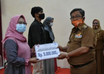 Bupati Gorontalo Utara, Indra Yasin, Indra Yasin, saat menyerahkan Bantuan Beasiswa kepada Mahasiswa yang melaksanakan Studi di Luar Daerah, bertempat di Dinas Pendidikan Gorontalo Utara, Senin (21/12/2020).