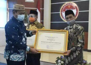 Asisten I Setda Provinsi Gorontalo, Syukri J Botutihe, menyerahkan piagam penghargaan Kanwil Kemenkumham Gorontalo kepada Bupati Gorontalo, Nelson Pomalingo, Senin (14/12/2020).