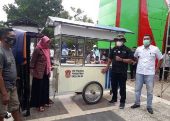 Sekda Ridwan Yasin saat menyerahkan bantuan Gerobak dan Tenda kepada pelaku usaha kecil di Kabupaten Gorontalo Utara, bertempat di RTH Gorut. Rabu, (16/12/20) (Foto : Sudin Lamadju/prosesnews.id)