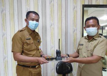 Pejabat lama Kadis Kominfo Wahyudin Katili (kanan) menyerahkan secara simbolis aset kantor kepada Kadis Kominfo yang baru Masran Rauf di sela-sela serah terima jabatan, Senin (18/1/2021). Masran Rauf sebelumnya menjabat Karo Humas dan Protokol, sementara Wahyudin dipercaya menjabat Kadis Dikbudpora Pemprov Gorontalo. (Foto: Alfred-Kominfo).