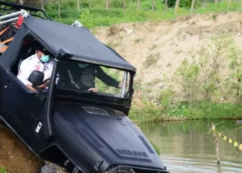 Gubernur Gorontalo Rusli Habibie ditemani putranya Zaenal Habibie, saat menunggangi mobil Jeep black satinnya yang bermesin Isuzu DMax Build up 3000 cc, melintasi derasnya arus sungai Bolango. Aksi Rusli ini saat melakukan offroad bersama pengurus dan anggota IOF, Sabtu (2/1/2021). (Foto : Salman)