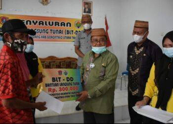 Bupati Gorut, Indra Yasin, saat menyerahkan BLT kepada warga di Desa Pontolo kabupaten Gorut. Jum'at, (22/01/2021).