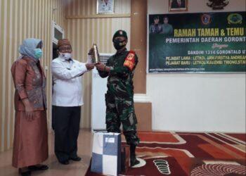 Bupati Gorut Indra Yasin, menerima Cendra Mata kenang-kenangan dari Eks Dandim Gorut, Letkol Arm. Fristya Andrean Gitrias. (Foto : Istimewa).