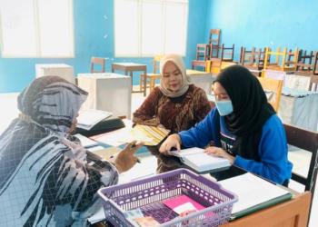 Ketua TPKK Provinsi Gorontalo Idah Syahidah saat mengambil rapor ujian semester milik putri bungsunya Siti Rahma Khirana Habibie, yang bersekolah di MTS Negeri 1 Kota Gorontalo, Selasa (12/1/2021). Sebelum mengambil rapor, Idah menyaksikan dulu sang putri saat tilawa al quran. (Foto – Riri)