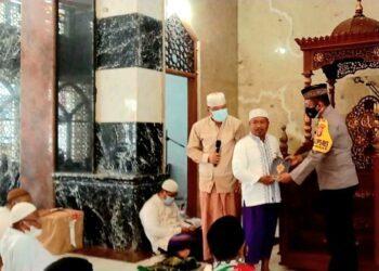 Wakapolres Boalemo, Kompol Nikson Yusuf, SH (kanan), saat menyerahkan Alquran kepada pengurus Masjid Baiturrahman Tilamuta. Jum'at, (19/02/2021). (Foto : Istimewa).
