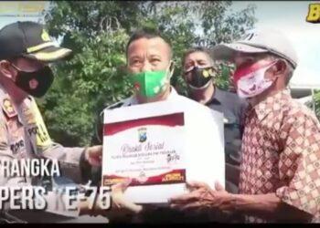 Kapolres Pasuruan, AKBP Rofiq Ripto Himawan, saat memberikan paket sembako kepada masyarakat.(Foto : Istimewa).