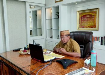 Sekretaris Daerah Provinsi Gorontalo Darda Daraba saat membuka Bimbingan Teknis (Bimtek) Penyusunan Laporan Standar Pelayanan Minimal (SPM) di lingkungan pemerintah provinsi dan kabupaten/kota tahun 2021 secara virtual dari ruangan kerjanya, Selasa (9/2/2021). (Foto: Nova-Kominfo)