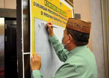 Wagub Gorontalo H. Idris Rahim menandatangani komitmen bersama dukungan percepatan penanganan COVID-19 pada rapat evaluasi program penanganan COVID-19 di Hotel Grand Q, Kota Gorontalo, Kamis (18/2/2021). (Foto : Haris)