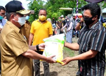 Wagub Gorontalo H. Idris Rahim (kiri) menyerahkan bantuan benih jagung kepada kelompok tani pada panen perdana dan pencanangan tanam jagung di Desa Butu, Kecamatan Tilongkabila, Kabupaten Bone Bolango, Senin (1/2/2021). (Foto : Haris)
