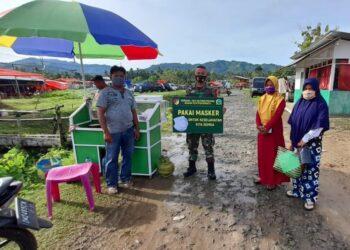 Babinsa Koramil Paguyaman, tampak memegang papan informasi, sebagai media sosialisasi kepada masyarakat pasar tradisional Molombulahe, Kecamatan Paguyaman. (Foto : Istimewa).