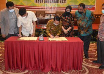 Bupati Gorontalo, Nelson Pomalingo, saat menandatangani MOU bersama Yayasan Semesta Otak Indonesia. Sabtu, (13/02/2021). (Foto : Istimewa).