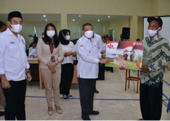 Wagub Gorontalo H. Idris Rahim (tengah) menyerahkan secara simboli Kartu Tani kepada seorang petani pada rakorev program pembangunan di Auditorium Kantor Bupati Bone Bolango, Rabu (3/3/2021). (Foto : Haris)