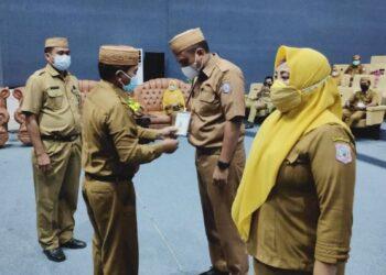 Sekretaris Daerah Provinsi Gorontalo Darda Daraba memasangkan kartu peserta kepada Pejabat Pengadaan usai membuka pelatihan dan ujian sertifikasi keahlian pengadaan barang dan jasa pemerintah (PBJP) di aula Badan Pelatihan dan Pendidikan (Diklat) Provinsi Gorontalo, Senin (22/3/2021). (Foto: ADC)