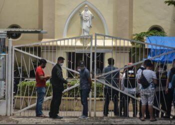 Polisi memeriksa lokasi di dekat sebuah gereja setelah ledakan di Makassarr (28/3/2021). polisi masih melakukan pengamanan di sekitar lokasi kejadian ledakan yang berada di Jalan Kartini Kota Makassar. (AFP/Indra Abriyanto)