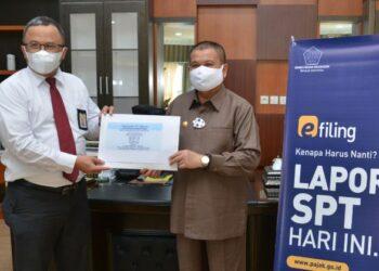 Wagub Gorontalo H. Idris Rahim (kanan) didampingi Kepala KPP Pratama Gorontalo, Suyono, menunjukkan bukti pelaporan SPT Tahunan. Wagub Idris Rahim melaporkan SPT Tahunan melalui aplikasi E-Filling di ruang kerjanya di Gubernuran Gorontalo, Senin (1/3/2021). (Foto : Haris)