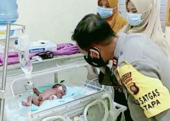 Kapolsek Tapa, Iptu Moch. Atmal Fauzi, saat melantunkan azan untuk bayi. (Foto : Istimewa).