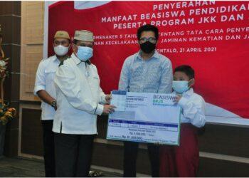 Wagub Gorontalo H. Idris Rahim (kiri) menyerahkan secara simbolis beasiswa pendidikan bagi peserta program JKK dan JKM BPJS Ketenagakerjaan di aula rumah jabatan Wagub Gorontalo, Rabu (21/4/2021). (Foto : Haris)
