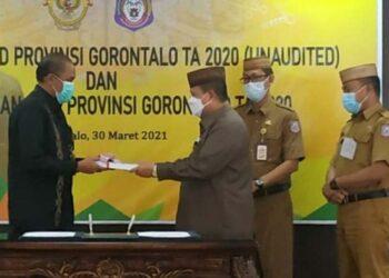 Wagub Gorontalo H. Idris Rahim (ketiga kanan), menyerahkan LKPD Unaudited Tahun Anggaran 2020 kepada Kepala BPK Perwakilan Provinsi Gorontalo di Kantor Perwakilan BPK Gorontalo, Selasa (30/3/2021). (Foto : Gusti)