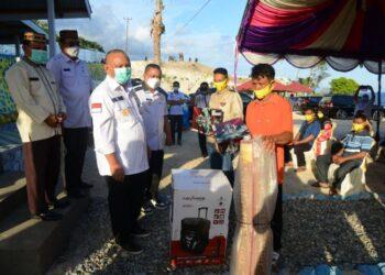 Gubernur Gorontalo Rusli Habibie saat menyerahkan bantuan karpet dan warles fortaybel kepada taqmirul masjid di Biluhu Timur, Rabu (21/4/2021). Bantuan ini diserahkan bersamaan dengan bantuan bahan pokok untuk 631 KPM terdampak covid-19 yang diwakili 15 KPM.  (Foto Salman)
