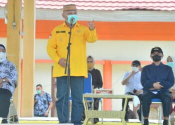 Gubernur Gorontalo Rusli Habibie saat memberikan sambutan pada pelaksanaan pasar murah di lapangan Buntulia Kabupaten Pohuwato, Sabtu (24/4/2021). Dikesempatan tersebut,  Rusli kembali mengingatkan untuk masyarakat yang berbelanja agar terus menerapkan prokes.  (Foto – Salman)