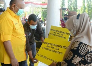 Gubernur Gorontalo Rusli Habibie (kiri), menyerahkan secara simbolis honor untuk bendaraha BOS tingkat SMA, SMK dan SLB di Alun-Alun Tilamuta, Kabupaten Boalemo, Minggu (25/4/2021). (Foto : Salman)