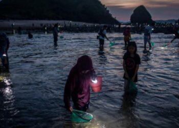 Sejumlah warga mencari dan mengumpulkan (cacing laut warna-warni) di Pantai Seger, Kawasan Ekonomi Khusus (KEK) Mandalika, Kuta, Praya, Lombok Tengah, Nusa Tenggara Barat (NTB), Kamis (4/3/2021). ANTARA FOTO/Aprillio Akbar