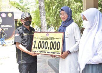 Bupati Pohuwato Saipul Mbuinga, menyerahkan  Bonus Pemuda berprestasi kepada Sevia, yang mewakili Provinsi Gorontalo di Paskibraka Nasional. (Foto : Istimewa)