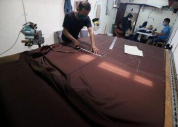 Pekerja membuat pola baju seragam sekolah pada lembaran kain di sebuah konveksi di Surabaya, Jawa Timur, Selasa (6/4/2021). ANTARA FOTO/Didik Suhartono