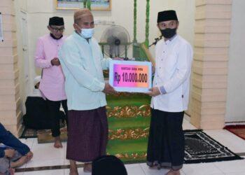 Bupati Pohuwato, Saipul Mbuinga (kanan), menyerahkan dana hibah secara simbolis kepada Takmirul Masjid Al-musyawarah. (Foto : Humas)