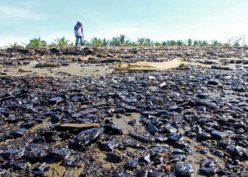 Warga melintasi pantai yang tercemar limbah batu bara. (Foto : SYIFA YULINNAS/ANTARA FOTO)