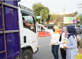 ASN Diskominfotik membagikan takjil kepada sopir truk yang melintas di Simpang Lima Telaga, Kota Gorontalo, Senin(10/5/2021). (Foto: Nova)