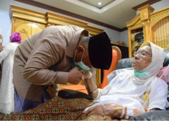 Gubernur Gorontalo Rusli Habibie mencium tangan ibundanya, Marie Sidiki saat berlebaran Idulfitri, Kamis (13/5/2021). Gubernur dua periode itu bersyukur masih bisa mencium tangan ibunya di hari yang fitri. (Foto: Salman).