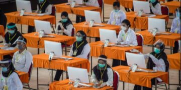 Peserta mengikuti ujian Seleksi Kompetensi Bidang (SKB) di Surabaya, Selasa (22/9/2020). Badan Kepegawaian Daerah (BKD) Kota Surabaya menggelar ujian SKB yang diikuti 1.142 peserta CPNS dengan menerapkan protokol kesehatan pencegahan COVID-19 secara ketat. (Juni Kriswanto/AFP)