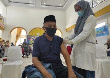 Ahmad Bait (72 tahun) saat mengikuti vaksinasi covid-19 bagi lansia di Bele Li Mbui Kota Gorontalo, Rabu (16/5/2021). Dinas Kesehatan Provinsi Gorontalo menggelar Gebyar Vaksinasi Lansia untuk mendorong percepatan penyuntikan vaksin bagi lansia. (Foto: Alfred).