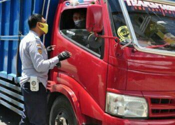 Seorang petugas dari Dinas Perhubungan Provinsi Gorontalo menyosialisasikan penutupan perbatasan kepada pengemudi kendaraan yang melintasi posko perbatasan di Kecamatan Atinggola, Kabupaten Gorontalo Utara, Sabtu (1/5/2021). (Foto : Haris)