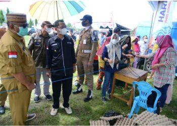 Gubernur Rusli saat memantau proses berjalannya pasar murah yang dilaksannakan di lapangan Desa Tolinggula Tengah, Kecamatan Tolinggula. (FOTO – SALMAN)