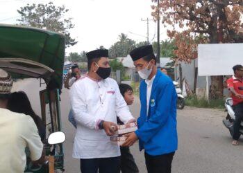 Momen Al Amin Uduala bersama Ketua PMII Cabang Pohuwato saat berbagi Takjil Ramadan (foto : istimewa)