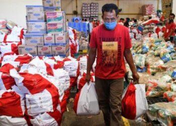Pekerja membawa paket bantuan sosial (bansos) yang akan disalurkan di Gudang Food Station Cipinang, Jakarta, Rabu (22/4).ANTARA FOTO/ M Risyal Hidayat