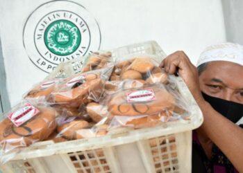 Pemilik industri rumah tangga Bolu Ria Jaya mengangkat kue yang sudah mendapat sertifikasi halal di Pekanbaru, Riau. ANTARA FOTO/ FB Anggoro