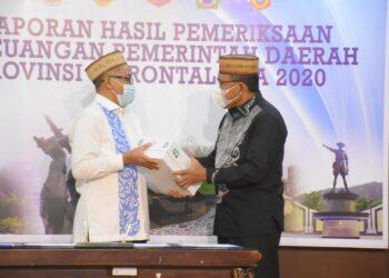 Plt Bupati Boalemo, Ir. Anas Jusuf, M.Si, (kanan), ketika menerima penghargaan Opini WTP dari Kepala BPK-RI Perwakilan Provinsi Gorontalo. (Foto : Humas)