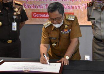 Bupati Gorontalo Utara Indra Yasin, saat melakukan penandatanganan persetujuan WBK dan WBBM bersama Forkopimda Gorontalo Utara di Rumah Saronde Hotel Aston Kota Gorontalo. (Foto : Istimewa).