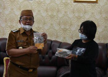 Indra Yasin memperlihatkan 2 keping emas bersejarah yang ditemukan oleh Balai Arkeologi Sulawesi Utara Manado. (Foto: istimewa)