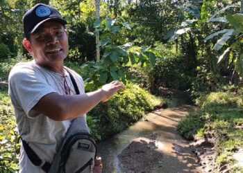 Salah seorang warga Desa Suka Mulya, Yon Maryono, menunjukan area normalisasi sungai yang tak teralisasi. (Foto : Majid Rahman/Prosesnews.id)
